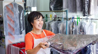 Dry cleaner handing clothing to a customer with a smile.